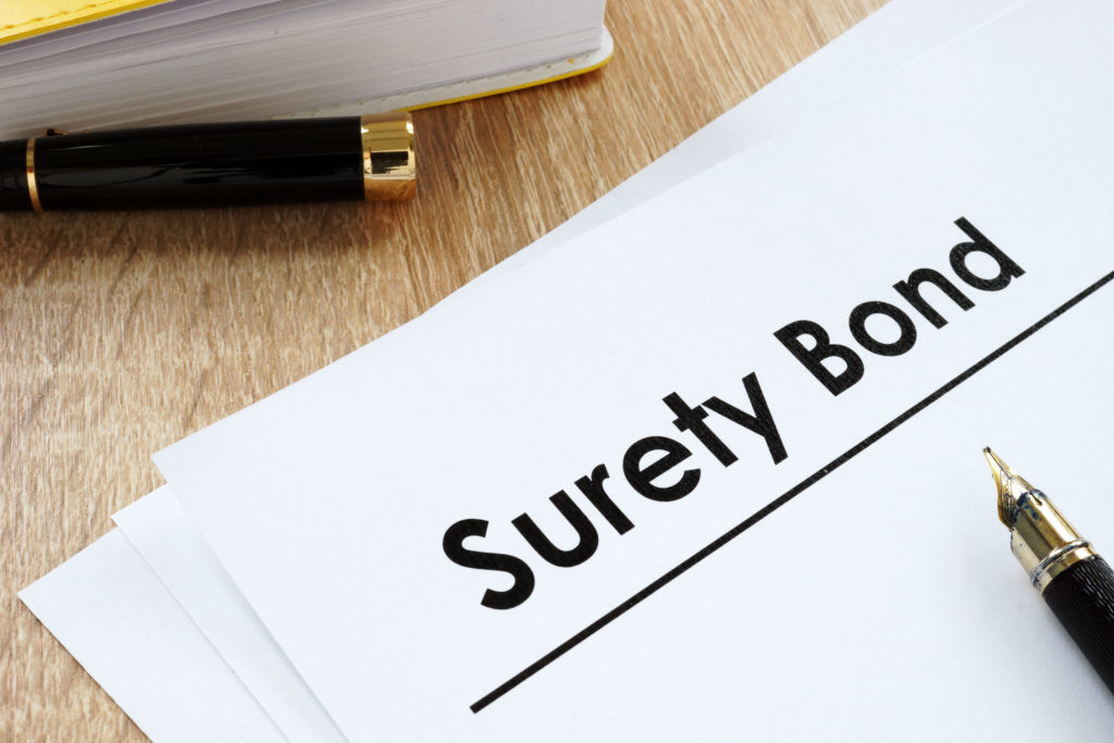 Surety bond form and pen on a table.