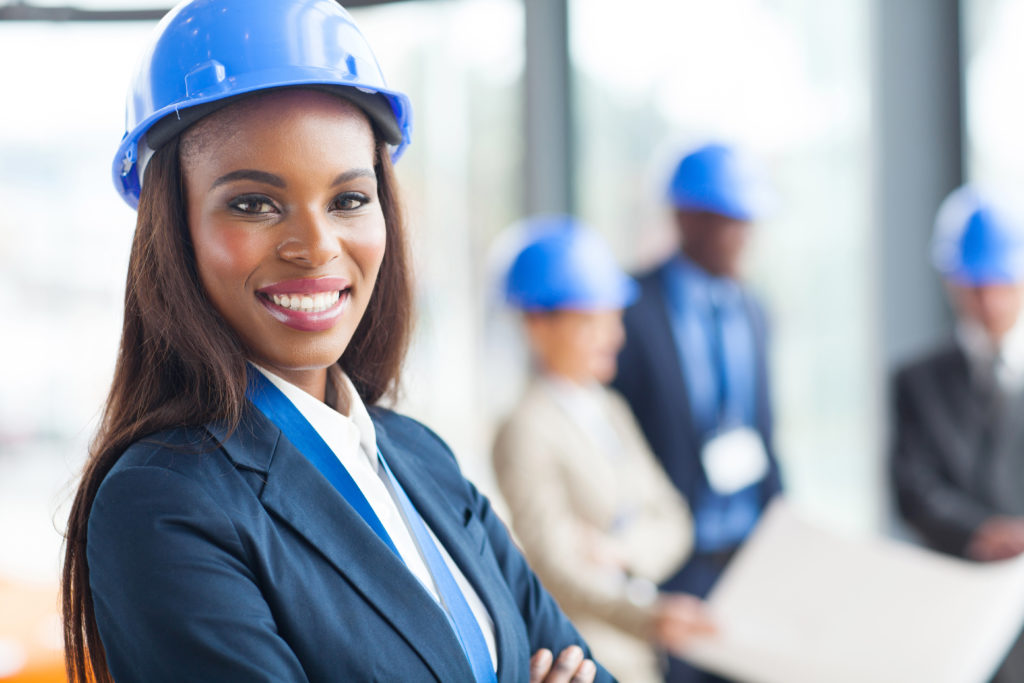 women-owned and minority-owned business owner wearing suit and hard hat
