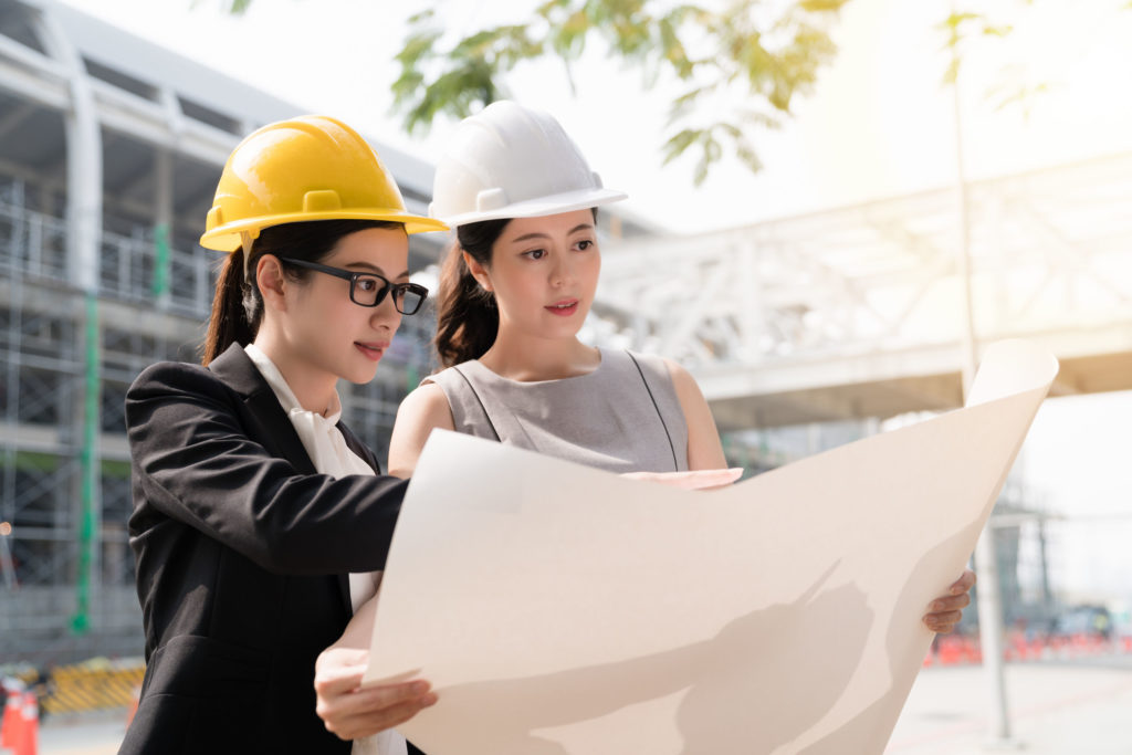 women- and minority-owned businesses. two female architects looking at building plans on construction site.